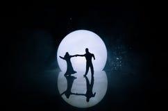 Sylwetki zabawkarski para taniec pod księżyc przy nocą Postacie mężczyzna i kobieta w miłości tanczy przy blaskiem księżyca Obraz Royalty Free