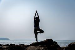 Sylwetkowa kobieta robi goa na plaży w Goa zdjęcie royalty free