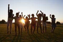 Sylwetkowa szkoła żartuje doskakiwanie outdoors przy zmierzchem obraz stock