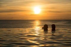 Sylwetkowe głowy przeciw nieskończoności krawędzi basenowi Fotografia Royalty Free
