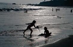 Sylwetkowi dzieci Bawić się na plaży Obraz Royalty Free