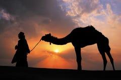 Sylwetkowy beduiński odprowadzenie z jego wielbłądem przy zmierzchem, Thar deser Obrazy Royalty Free