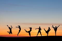 Sylwetkowy grupowy bębnowanie i taniec w zmierzchu obraz stock