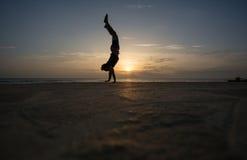 Sylwetkowy mężczyzna robi handstand w zmierzchu zdjęcia royalty free