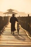 Sylwetkowy mężczyzna spacerów rower wzdłuż drewnianego footbridge Obraz Stock