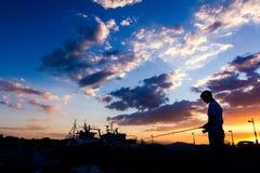 Sylwetkowy strzał chłopiec połów na molu przy zmierzchem Fotografia Stock