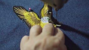 Symaskin för damskräddarebruk för att sy örnsymbollappen lager videofilmer