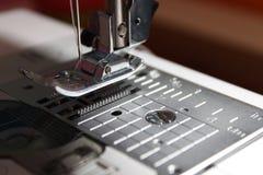Symaskinpresserfoten lyftte med synlig matningshundkapplöpning Arkivfoton