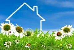 Symbol av ett hus på grönt soligt fält Arkivfoto