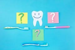 Symbol av frågefläcken från tandkräm och tandborsten på blå bakgrund, fotografering för bildbyråer