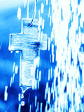 Symbol of Baptism - Cross under water shower. A symbol of christian baptism - small wooden hand made cross in an open air shower. Blue Stock Images