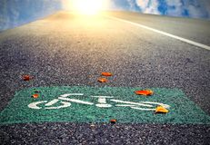 The symbol of the bike lane on the street. There is a sky, orange light and the sun as the background. The concept of using effects to convey feelings Stock Photography