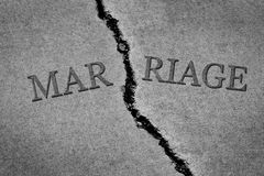 Symbol of broken marriage with crack in concrete and word. Symbol of broken marriage with crack in concrete concept of end of relationship Stock Image
