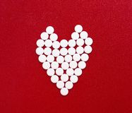 Symbol of care. White tablets in form of heart on red background stock photography