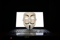 Symbol of computer hackers. A 'V for Vendetta' or anonymous mask on a laptop computer stock photo