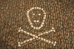 Symbol of crossed bones and skull created from white cobbles on the ground Stock Photo