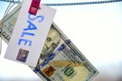 Symbol des Verkaufsdollars hängend an einem Seil mit einer Klemme 100 Lizenzfreie Stockfotografie