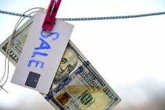Symbol des Verkaufsdollars hängend an einem Seil mit einer Klemme 100 Stockfoto