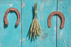 Symbol des Weizenbündels und des Glücks mit zwei Hufeisen auf hölzerner Scheunenwand Stockbild
