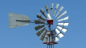 Old vintage style windmill rotating on a sunny day with blue sky background.