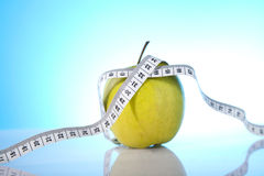 Symbol of diet. Green apple with measuring tape Royalty Free Stock Photos