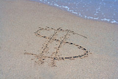 Symbol for dollar ($) written in sand. A sandy beach with a dollar sign $ written in the sand and small wave Royalty Free Stock Photo