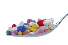 Symbol of drugs dependency. Spoon full of colored pills and tablets-symbol of drugs addiction Royalty Free Stock Images