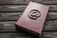 Symbol of e-mail on a book on a wooden background. royalty free stock photos