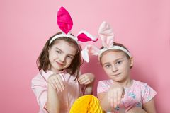 Two little friends, with Bunny ears, depict Easter rabbits. The symbol of Easter.Two girls with ears on their heads and a big yellow egg. On a pink background stock image