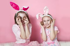 Two little friends, with Bunny ears, depict Easter rabbits. The symbol of Easter.Two girls with ears on their heads and chocolate eggs on a pink background stock photo
