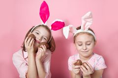 Two little friends, with Bunny ears, depict Easter rabbits. The symbol of Easter.Two girls with ears on their heads and chocolate eggs on a pink background royalty free stock photography