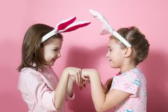 Two little friends, with Bunny ears, depict Easter rabbits. The symbol of Easter.Two girls with ears on their heads. On a pink background royalty free stock photography