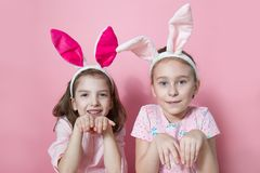 Two little friends, with Bunny ears, depict Easter rabbits. The symbol of Easter.Two girls with ears on their heads. On a pink background royalty free stock images