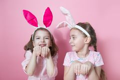 Two little friends, with Bunny ears, depict Easter rabbits. The symbol of Easter.Two girls with ears on their heads. On a pink background royalty free stock photo