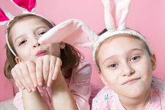 Two little friends, with Bunny ears, depict Easter rabbits. The symbol of Easter.Two girls with ears on their heads. On a pink background royalty free stock image