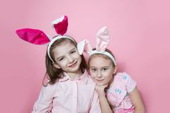 Two little friends, with Bunny ears, depict Easter rabbits. The symbol of Easter.Two girls with ears on their heads. On a pink background royalty free stock photos