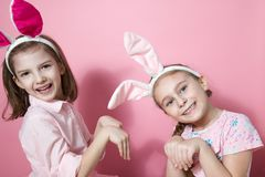 Two little friends, with Bunny ears, depict Easter rabbits. The symbol of Easter.Two girls with ears on their heads. On a pink background stock photos