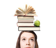 Symbol of education. On the head of a young girl lies stop books and an apple. Symbol of education stock image