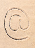 AT symbol, email address icon drawn on sand Stock Photos