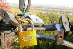 A yellow lock as a symbol of endless love and devotion on the background of noble city, Kiev. A symbol of eternal love in marriage. Yellow navesenoy metal lock Royalty Free Stock Photos