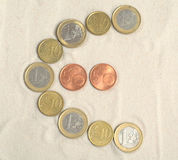 Symbol of euro with euro coins. On the sand Royalty Free Stock Photo