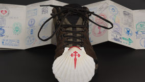 Symbol fo El Camino - Pilgrimage. Shell next to the boot, symbol of pilgrimage and the pilgrim passport in the back filled up wiith stamps Royalty Free Stock Images