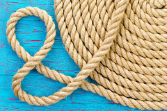 And symbol formed from a new coiled rope. And symbol formed from a loop in a new neatly coiled round rope over a crackle paint wooden blue background in a close Stock Photo