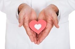 Symbol för doktor Holding Heart Shape Arkivbilder