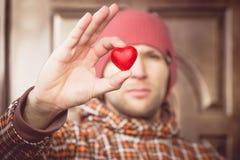 Symbol för hjärtaformförälskelse i manhand med framsidan på romantisk hälsning för bakgrundsvalentindag Royaltyfri Bild