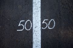 Symbol of gender equality on asphalt. Symbol of gender equality 50/50 on asphalt stock photos