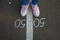 Symbol of gender equality 50/50 on asphalt. Gender concept royalty free stock photos