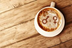 Symbol of gender equality on the coffee foam in wooden table. Concept of gender equality stock image