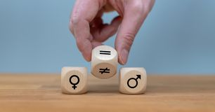Symbol for gender equality. Hand turns a dice and changes a unequal sign to a equal sign between symbols of men and women royalty free stock image