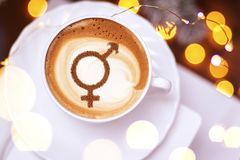 Symbol of gender equality. On milk foam coffee cups cappuccino royalty free stock photography